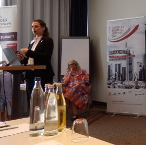 Helene Proelß, owner of foundation, is assisted by Corinna Prange, volunteer @ Managers Without Borders Foundation gGmbH, standing in front of her audience.